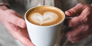 a person holding a cup of coffee with frothed milk in the shape of a heart
